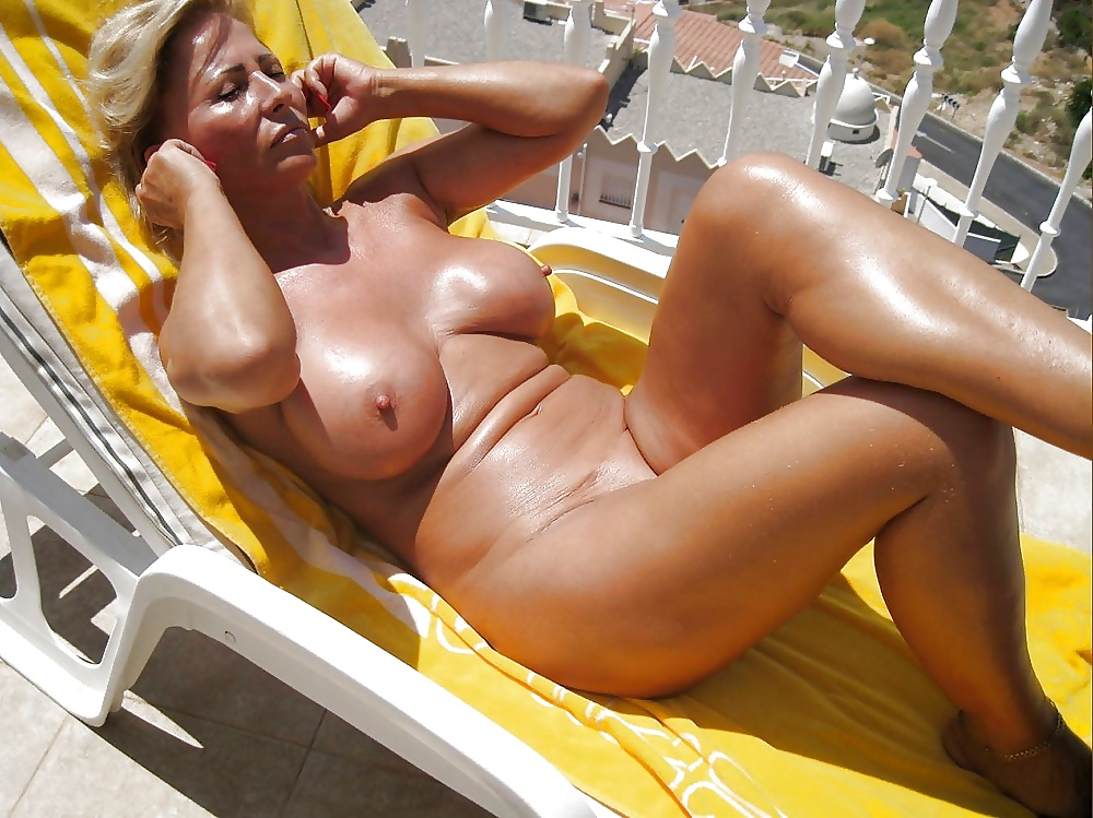 Oiled up beauty tans naked in the sun