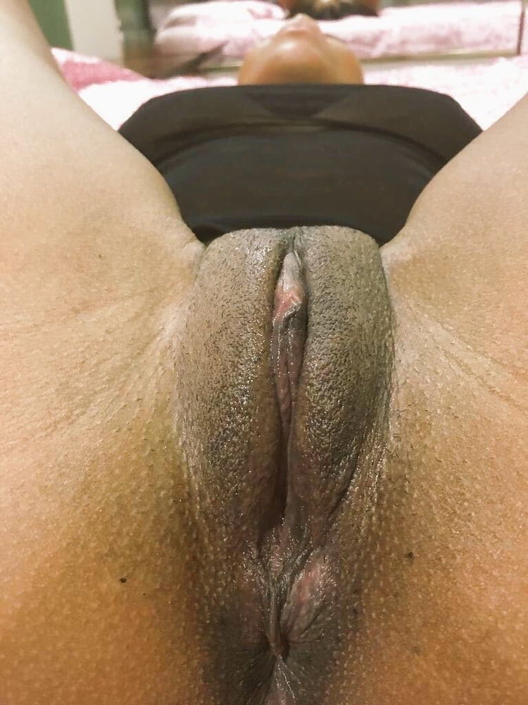 She spreads her legs and her dark hairy pussy lips